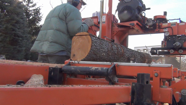 The log can then be rotated 90 degrees and reclamped against the side supports. This second cut is also waste.
